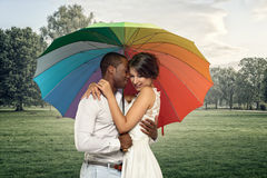 Giovani coppie dolci sotto un ombrello variopinto Immagine Stock