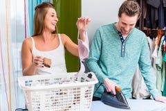 Giovani coppie, donna ed uomo, dividenti lavoro domestico e facenti il lau immagine stock