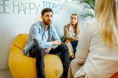 Giovani coppie durante il consiglio psicologico con lo psicologo immagini stock libere da diritti