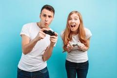 Giovani coppie emozionanti, un tipo e una ragazza, con le leve di comando in loro mani che giocano i video giochi su un fondo blu fotografie stock