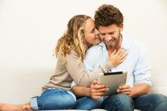 Giovani coppie facendo uso del computer della compressa fotografia stock