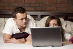 Giovani coppie facendo uso del computer portatile Fotografia Stock