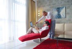 Giovani coppie facendo uso del computer portatile a casa Immagine Stock