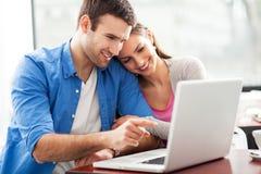 Coppie che esaminano computer portatile Immagini Stock Libere da Diritti