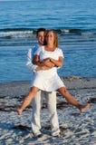 Giovani coppie felici alla spiaggia Immagine Stock