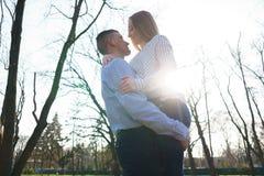 Giovani coppie felici che abbracciano al fondo soleggiato Gioventù, happine immagine stock libera da diritti