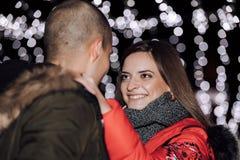 Giovani coppie felici che abbracciano alla notte fotografia stock