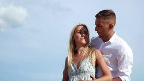 Giovani coppie felici che abbracciano e che baciano sul fondo del cielo blu Concetto romantico HD, 1920x1080 video d archivio