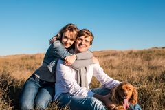 Giovani coppie felici che abbracciano e che ridono all'aperto immagine stock libera da diritti
