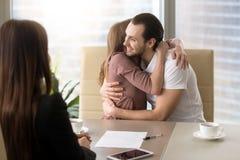 Giovani coppie felici che abbracciano sulla riunione con l'agente immobiliare Fotografia Stock Libera da Diritti