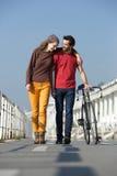 Giovani coppie felici che camminano all'aperto con la bici Fotografie Stock
