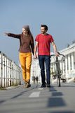 Giovani coppie felici che camminano all'aperto indicando Fotografia Stock