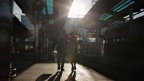 Giovani coppie felici che camminano sul binario della stazione ferroviaria al treno all'ultima luce del sole, stock footage