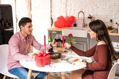 Giovani coppie felici che celebrano giorno del ` s del biglietto di S. Valentino con un regalo immagine stock