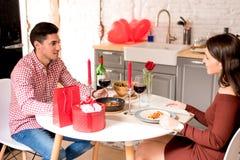 Giovani coppie felici che celebrano giorno del ` s del biglietto di S. Valentino con una cena a casa immagini stock libere da diritti