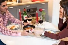 Giovani coppie felici che celebrano giorno del ` s del biglietto di S. Valentino con una cena a casa immagine stock