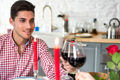 Giovani coppie felici che celebrano giorno del ` s del biglietto di S. Valentino con una cena a casa che tosta con il vino fotografia stock
