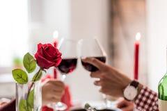 Giovani coppie felici che celebrano giorno del ` s del biglietto di S. Valentino con una cena a casa che tosta con il vino fotografia stock libera da diritti
