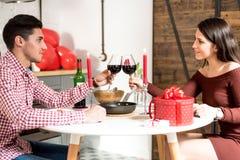 Giovani coppie felici che celebrano giorno del ` s del biglietto di S. Valentino con una cena a casa che tosta con il vino immagini stock