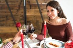 Giovani coppie felici che celebrano giorno del ` s del biglietto di S. Valentino con una cena a casa e un pane tostato fotografie stock libere da diritti