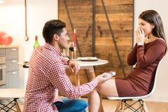 Giovani coppie felici che celebrano proposta di impegno con una cena a casa e un regalo fotografia stock