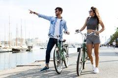Giovani coppie felici che ciclano nella città fotografia stock