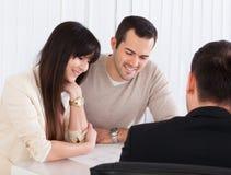 Giovani coppie felici che discutono con il consulente fotografia stock