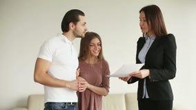 Giovani coppie felici che discutono contratto e che stringono le mani con l'appaltatore archivi video