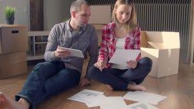 Giovani coppie felici che disimballano le scatole a loro nuova casa e che scelgono mobilia sul computer portatile