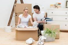 Giovani coppie felici che disimballano nella loro nuova casa fotografie stock libere da diritti