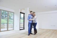 Giovani coppie felici che esaminano i dettagli di nuova casa immagini stock