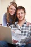 Giovani coppie felici che esaminano le finanze sul computer portatile immagine stock libera da diritti