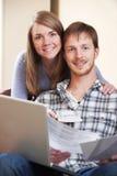 Giovani coppie felici che esaminano le finanze sul computer portatile fotografie stock libere da diritti
