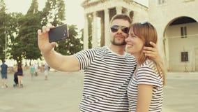Giovani coppie felici che fanno selfie con un telefono dello smat sulla vacanza stock footage