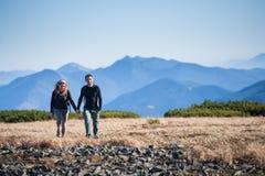 Giovani coppie felici che fanno un'escursione nelle belle montagne Fotografie Stock