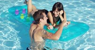 Giovani coppie felici che galleggiano sul materasso in stagno video d archivio