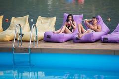 Giovani coppie felici che godono con le bevande sulle chaise-lounge attenuate dalla piscina sui precedenti del fiume immagine stock