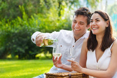 Giovani coppie felici che godono dei vetri di vino bianco Immagini Stock Libere da Diritti