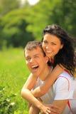 giovani coppie felici che godono del backriding all'aperto immagini stock
