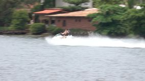 Giovani coppie felici che godono e che si divertono della guida su un jet ski video d archivio