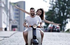 Giovani coppie felici che guidano un motorino nella città un giorno soleggiato Immagini Stock