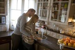 Giovani coppie felici che lavano i piatti immagine stock