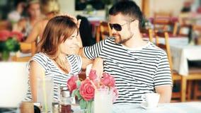 Giovani coppie felici che mangiano caffè in un caffè della via sulla loro vacanza stock footage