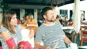 Giovani coppie felici che mangiano caffè in un caffè della via sulla vacanza archivi video