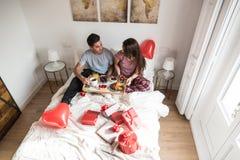 Giovani coppie felici che mangiano una prima colazione sorprendente sul letto fotografia stock libera da diritti