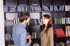 Giovani coppie felici che parlano dentro la biblioteca Fotografia Stock Libera da Diritti