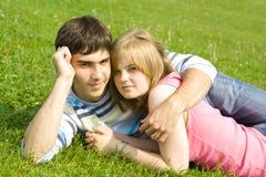 Giovani coppie felici che pongono su un'erba verde Fotografia Stock