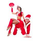 Giovani coppie felici che portano i vestiti del Babbo Natale Fotografie Stock Libere da Diritti