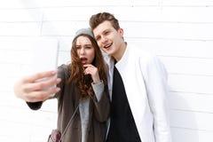 Giovani coppie felici che prendono selfie con il telefono cellulare Immagine Stock