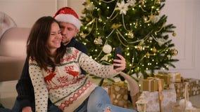 Giovani coppie felici che prendono selfie dentro decorato per la stanza di Natale Concetto di nuovo anno felice Famiglia bella video d archivio